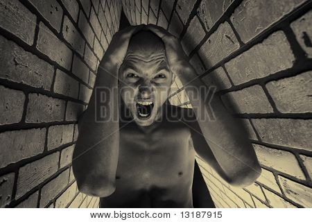 Portrait of a muscular man posing in a closed space over black background and brick wall.