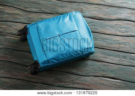 Blue luggage bag on wheels. Suitcase on green wooden background. It's time to leave. Don't forget your baggage.