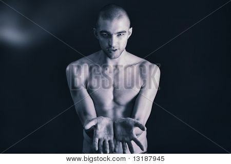 Portrait of a handsome muscular man posing over black background.