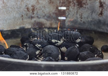 black coal briquettes in smoke at barbecue place