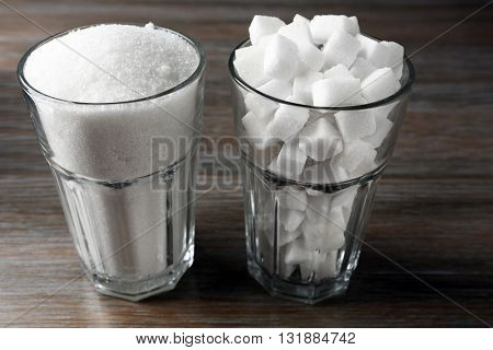 Highball glasses with granulated and lump sugar on wooden table