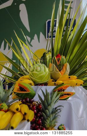 A display of tropical fruits, with bananas, pineapple, fronds, grapes, cantaloupe