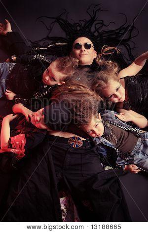 Heavy metal musician  with children lying on a floor. Shot in a studio.