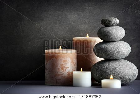 Composition of spa pebbles and candles on grey background