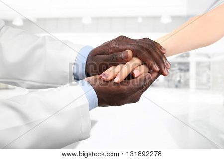 Male doctor holding patient's hand, on blurred background