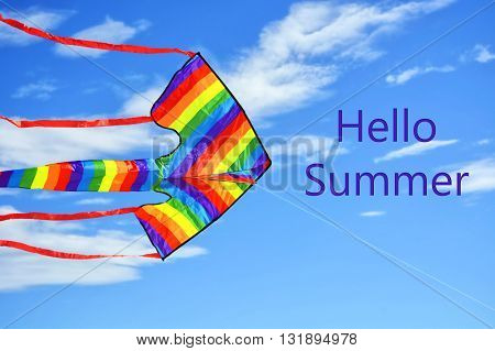Rainbow Coloured Kite Against Blue Skies.