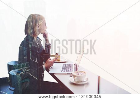 Double exposure with hipster girl with mobile phone thoughfull look away while is sitting at the table of modern coffee shop with open laptop computer. Woman freelancer using cell phone and net-book