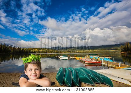 beautiful seven year old boy in a carnival wearing a crown of shiny green leaves. He sits astride a chair Wooden boat dock with moored pleasure boats and benches. Pyramid mountain and Pyramid Lake