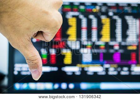Trader acting Bad Hand on market monitor background.