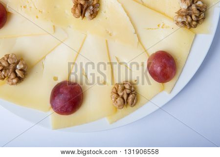 Cheese sliced with nuts and grapes served on a plate