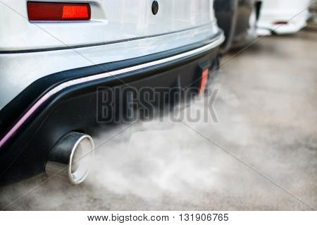 combustion fumes coming out of car exhaust pipe.
