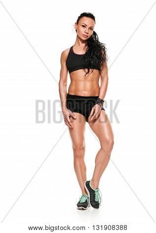 Full length portrait of fit young woman in sports wear standing on white background. Muscular fitness model.