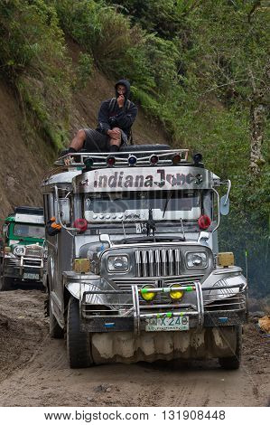 BANAUE PHILIPPINES - JANUARY 25 2014: Local public transport jeepney driving fast along a dirt road in the mountain province of banaue in northern luzon in the philippines