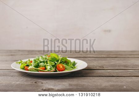 Plate of fresh salad on wooden table with free place on the table on a light background