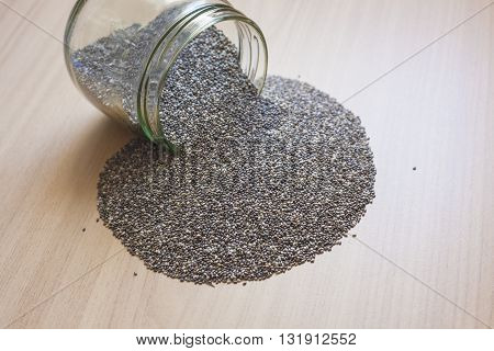 Glass jar with chia seeds spilt over wooden surface. Selective focus
