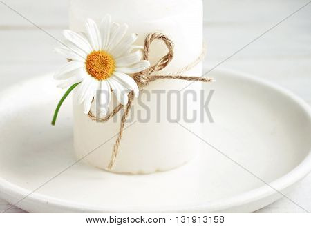 Candle decor simple summertime style. Candlestick decorated fresh daisy flower. Soft light and focus.