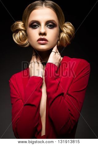 Beautiful girl in a red dress with a deep neckline and black rings on his fingers. The model with bright makeup. Photo was made in a studio.