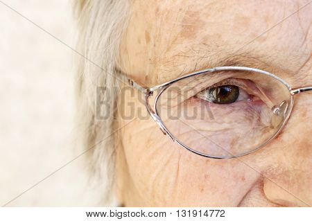Close-up of old woman's eye with glasses