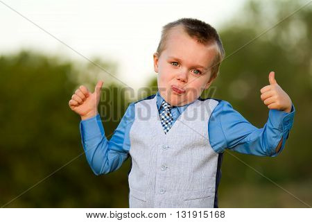 In a suite and tie little boy sticks his tongue out and sticks up his thumbs