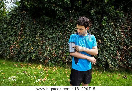 Running workout man with mp3 music player listening to music with mp3 player armband with smart mobile phone. poster