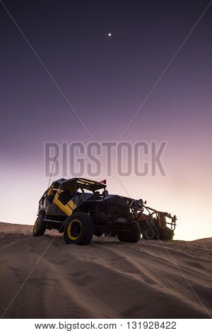 buggy on sand dunes at purple sunset in huacachina, peru