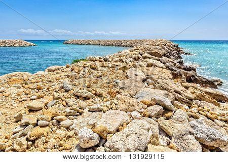 Row of rocks and stones as weir in greek ocean