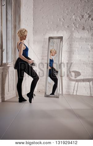 Female ballet dancer practicing front of mirror in studio.