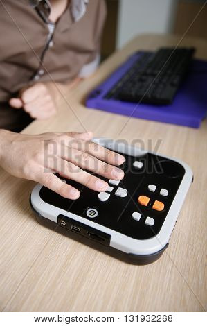 Blind person using audio book player for visually impaired listening to audio book on his computer. Blindness aid visual impairment independent life concept.