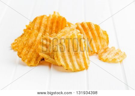 Crinkle cut potato chips on table. Tasty spicy potato chips.