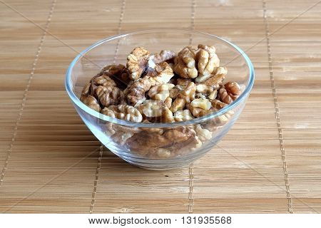 Images containts corn kernels walnuts in a glass on a bamboo napkin