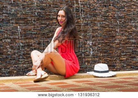 Young slim girl sitting on a background of falling water on a sunny summer day. Resort.