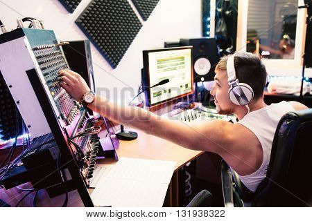DJ adjusts equipment in the  sound recording studio. DJ adjusts music equipment before starting record club music.  Composer checks sound panel . Digital sound equipment service concept poster