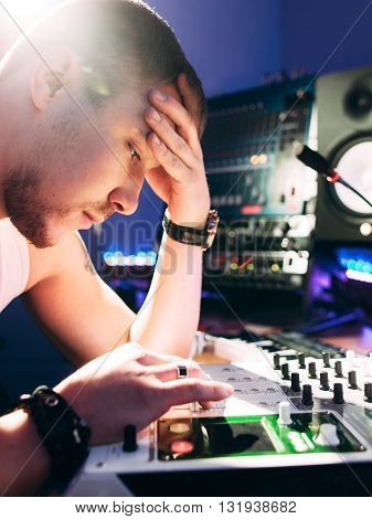 DJ adjusts equipment in the recording studio. DJ adjusts music equipment before starting work.  Composer checks sound panel .
