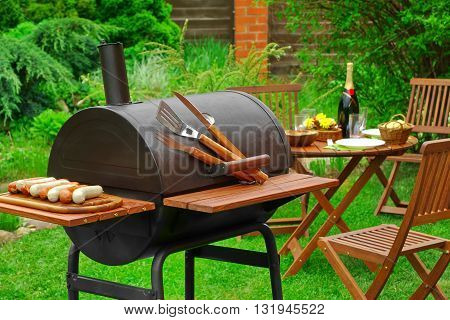 Summer Weekend BBQ Scene With Charcoal Grill On The Backyard Lawn And Outdoor Wooden Furniture In The Background poster