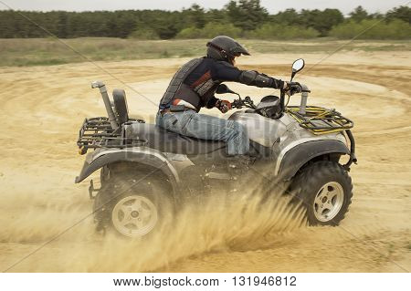 Man involved in ATV racing on the sand.