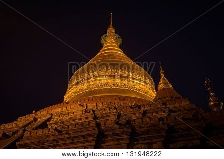 Night scene of the Shwezigon golden pagoda famous for its gold-leaf stupa in Bagan ancient city of Myanmar Burma