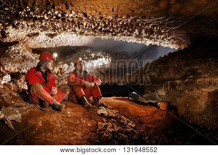 Cavers exploring a beautiful newly discovered cave poster