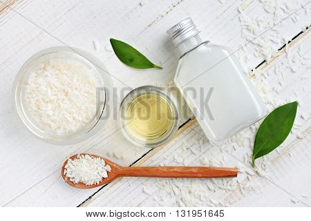 Coconut cosmetic products. Coconut shavings, oil, milk. Healthy skincare. Top view background.