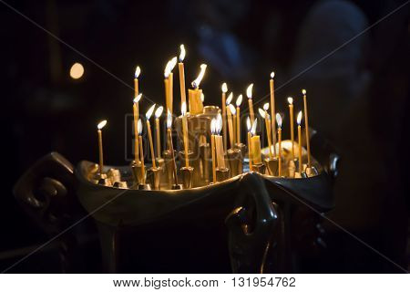 Man hand lighting candles in a church. he candles in Georgian Church. Long lighted candles group on black background.
