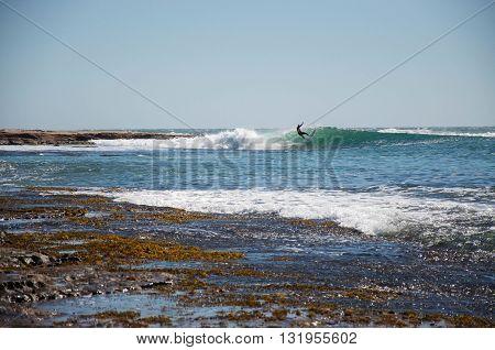 KALBARRI,WA,AUSTRALIA-APRIL 20,2016: Surfing the rocky left point break in Indian Ocean waves at Jake's Point with in Kalbarri, Western Australia.