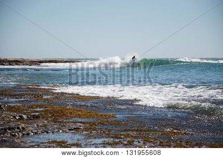 KALBARRI,WA,AUSTRALIA-APRIL 20,2016: Tourist surfing the the Indian Ocean waves at risky and rocky Jake's Point on a clear day in Kalbarri, Western Australia.