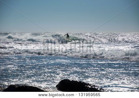 KALBARRI,WA,AUSTRALIA-APRIL 20,2016: Surfer riding the glistening waves of the Indian Ocean at Jake's Point in Kalbarri, Western Australia.