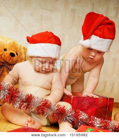 Two adorable toddlers in Christmas hats packing presents