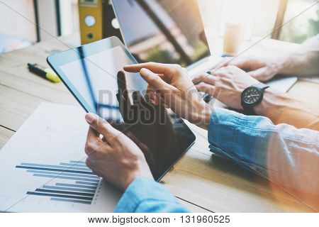 Woman Touching Digital Tablet Hand.Reflections Screen.Project Producers Researching Process.Young Business Crew Working with New Startup Studio. Blurred, film effect. Horizontal closeup photo