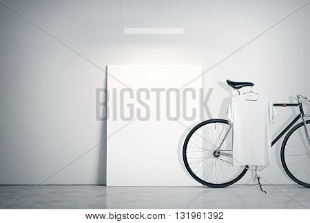 Photo Interior Modern Studio Loft with Concrete Wall and Classic bicycle.Empty White Canvas on Floor, Spotlight top. Blank Tshirt hanging Bike. Horizontal mockup