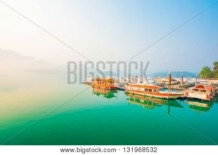 Sun Moon Lake Yuchi Nantou county Taiwan - March 21 2015 : Sunrise View of Sun Moon Lake with the passenger boats waiting at the numerous piers