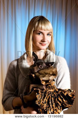 Elegant girl with funny little dog in luxury dog's clothing poster