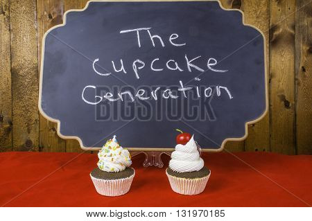 two cupcakes on red in front of black chalkboard written the cupcake generation with wood background