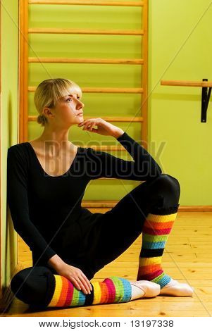Beautiful ballet dancer sitting on a floor and relaxing after exercise