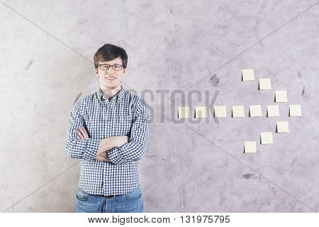 Smiling caucasian man with crossed arms standing next to sticker arrow glued onto concrete wall